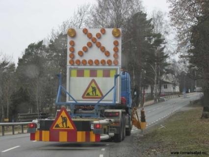 Bil som plockar upp de orange snöröjningspinnarna