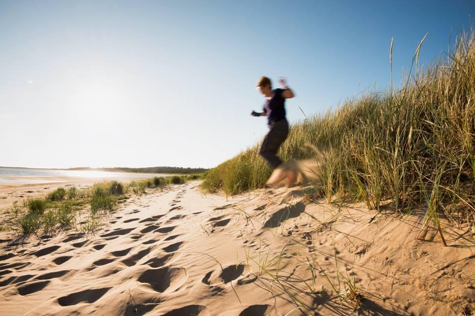 kristina-hoppar-i-sanddyner-foto-johan-gustavsson