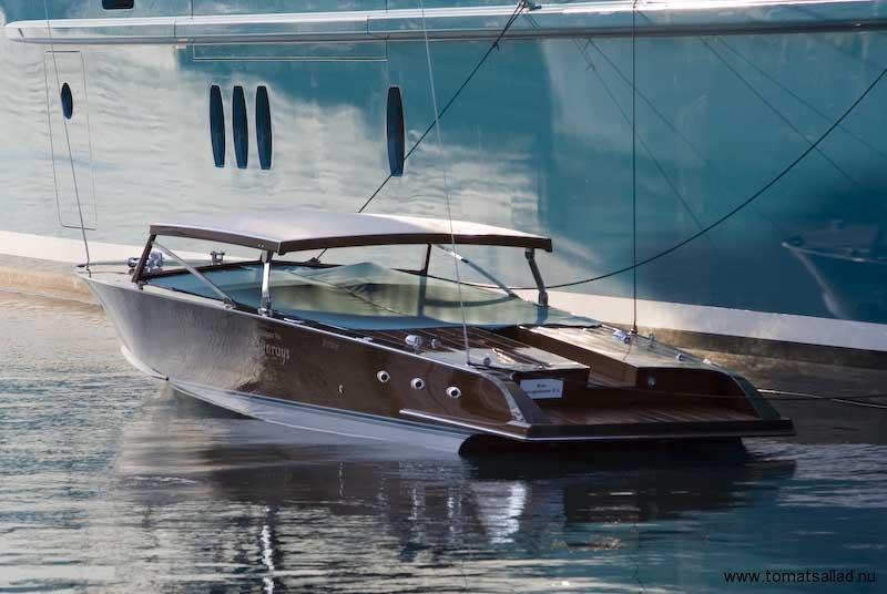 Liten båt vid en stor yacht