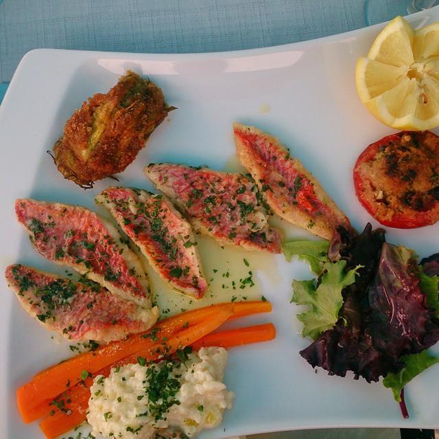 Galet bra mat på en restaurang som utifrån ser ut som en korsning mellan husvagn och container från 1960-talet. På tallriken #rouget dvs #rödbarb med en klick citronrisotto, persiljesmör, friterad och fylld #squashblomma och en #tomatfarcis Bordsbokning behövs. #legrandlarge #VilleneuveLoubet #RuntAntibes #MittNice