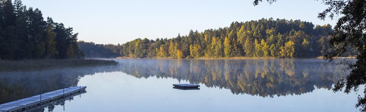 Spegelblank sjö med spår av morgondimma. Brygga till vänster.